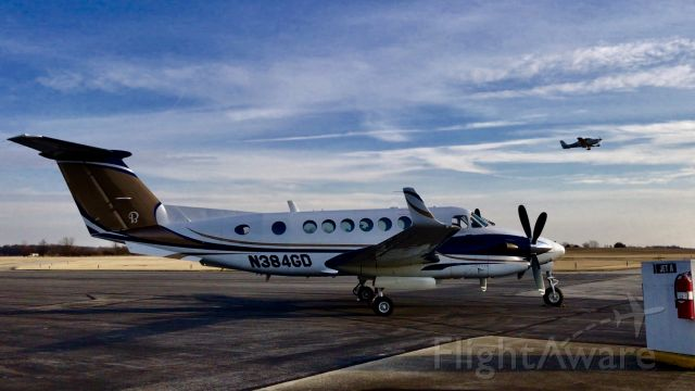 Beechcraft Super King Air 350 (N384GD) - A king Air sits on the ramp as a Cirrus SR22 departs to the west.