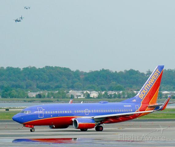 Boeing 737-700 (N258WN) - Note the two Ospreys flying in the upper left corner.