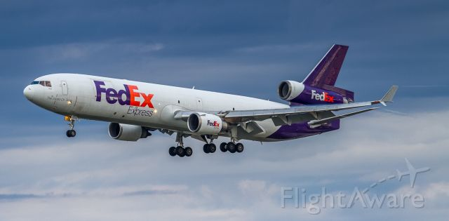 Boeing MD-11 (N574FE) - Just a hint of fluff on the wing and trailing a whisper of vortex off the winglet, this FEDEX MD11 about to land on 24R