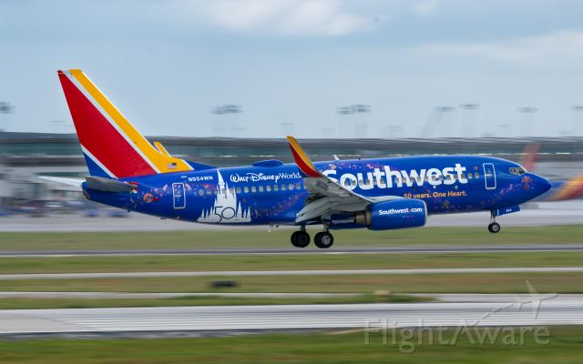 Boeing 737-700 (N954WN) - Southwest Airline's latest special livery, celebrating 50 years of partnership with Disney, arrives from New Orleans into Houston Hobby on a wet 30 Sep 2021 morning.  Taken from 1940 Air Terminal Museum balcony.