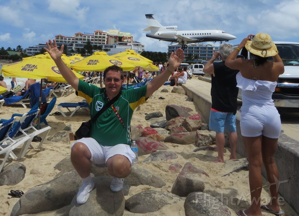 Dassault Falcon 900 (N909CK) - Balancing a Dassault Falcon 900 on my middle finger at Maho Beach, St Maarten, while cheering for our South African Protea Cricket team!