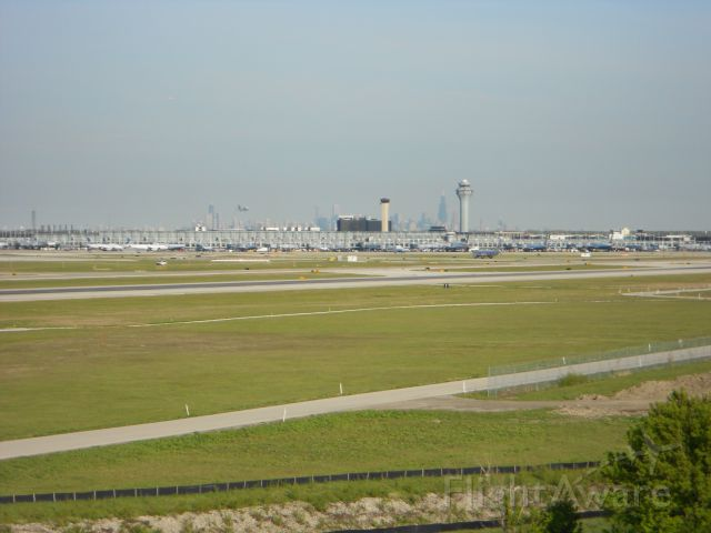 — — - View of KORD control towers, with Chicago skyline in background.