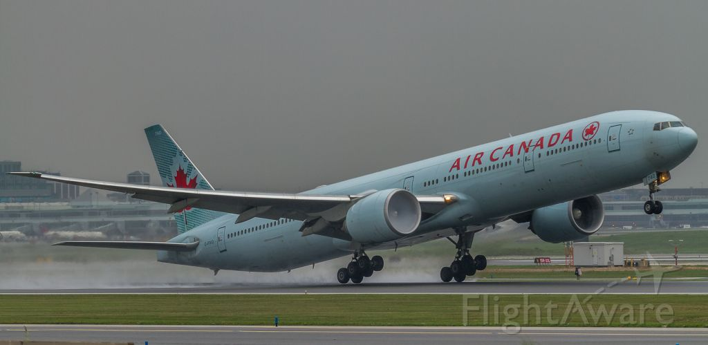 BOEING 777-300 (C-FIVQ) - Grim day for plane photography at YYZ… ACA87 lifts off a wet runway 23 on the start of her 14 hour journey to Shanghai with some fog brewing in the number two engine...