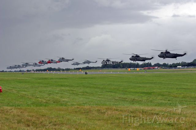 — — - A long line-up of helos saluting the crowds at RAF Fairford, UK.