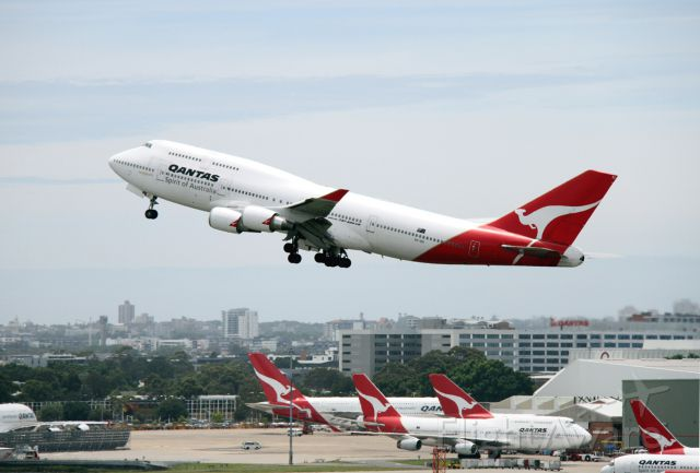 Boeing 747-400 (VH-OEI) - A 744 climbs out with more Qantas jumbos in the background: 744s and A380s.