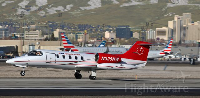 Learjet 35 (N325NW) - The pilot shields his eyes from the sun as he rotates N325NW off Runway 16L.