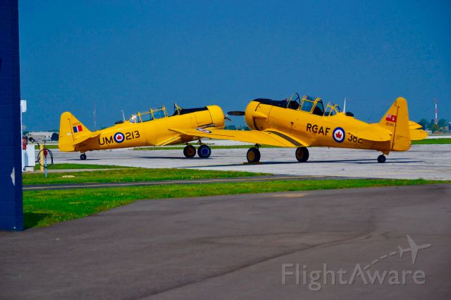 """— — - Two """"Harvards"""" sitting on the ramp at """"Windsor International Airport""""."""