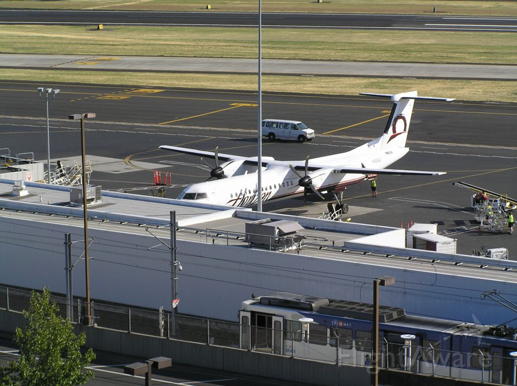 de Havilland Dash 8-400 (N4260X) - On the parking deck at PDX toward 25L-7R; note Tri-Met MAX light-rail car in foreground, serving PDX from downtown on the Red Line. 2009-07-02, around midday.