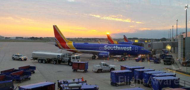 Boeing 737-800 (N8686A) - Rising sun kisses the tail of Southwest planes getting ready for passengers at Terminal A, Bradley Airfield.