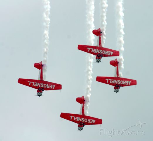 — — - The Aeroshell aerobatic team stays in perfect formation on the downside of their 4-ship loop.