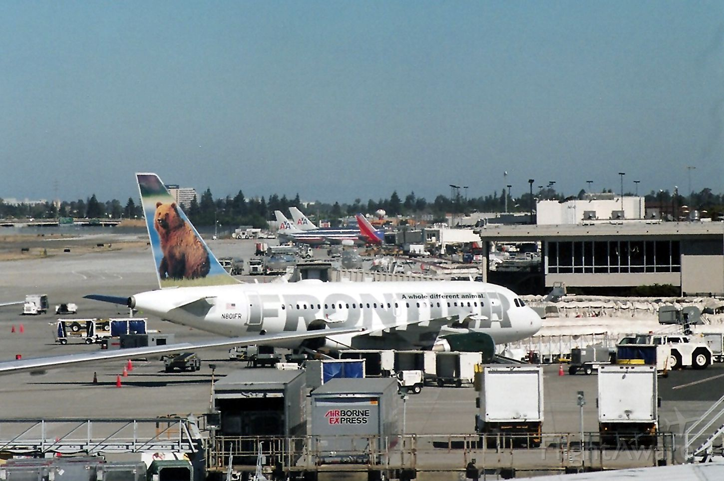 Airbus A318 (N801FR) - KSJC - early AM activity at San Jose - note the old Terminal C and the new Termnal B has not been built yet. View looking north, July 2004