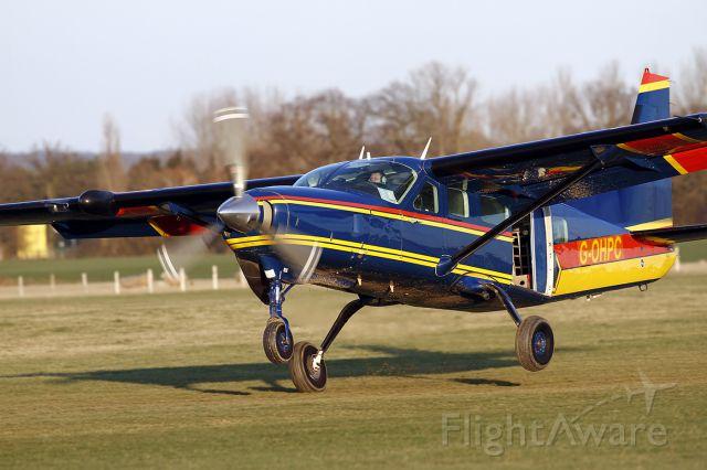 G-OHPC — - [cn.20800224]. Cessna 208 caravan G-OHPC action landing on the muddy grass strip after delivering Skydivers to their drop at Lashenden EGKH Headcorn Aerodrome Kent UK 19.2.2012.