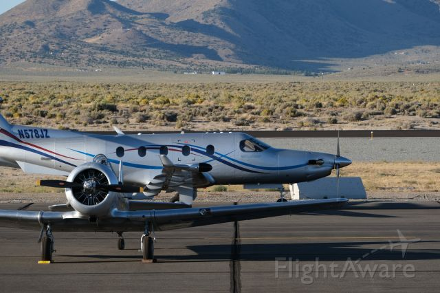 Pilatus PC-12 (N578JZ) - Pilatus taxiing past a slick silver North American T-6 at the National Air Races in Reno, Stead. One of my favorites.