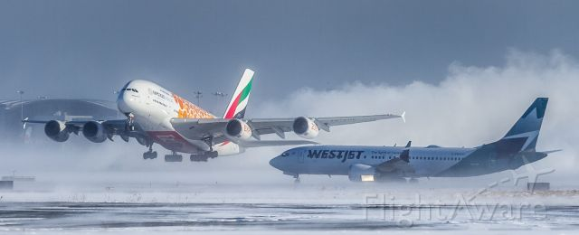 Boeing 737 MAX 8 (C-FNWD) - This Westjet Max8 holds short of the active as an Emirates A380 in the gold Expo 2020 (A6-EOE) livery gets airborne off runway 33R at YYZ kicking up a huge snow cloud behind her!