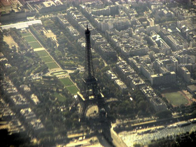 — — - On our flight back home from Istanbul via Paris we flew over over the Eiffel Tower.  Unfortunately I had the sun on my window, so there is this bluish haze, and as it was close to the lower edge of the window there is a lot of distortion.