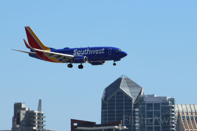 Boeing 737-700 (N778SW) - Southwest landing with new livery. San Diego skyline visible in the background.