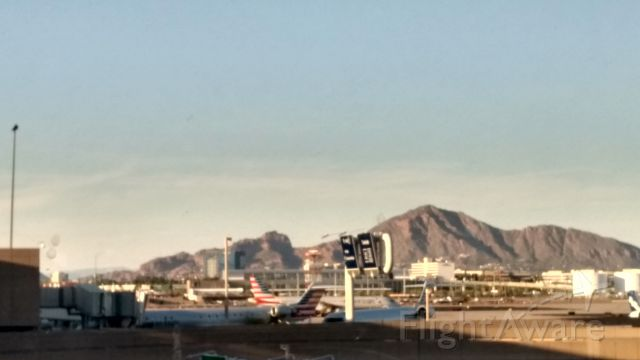 — — - Here is a photo from the east-side of Phoenix Sky Harbor Airport, Terminal 4. Some American Eagle jets are parked at the gates, and in the background is the Camelback Mountains.