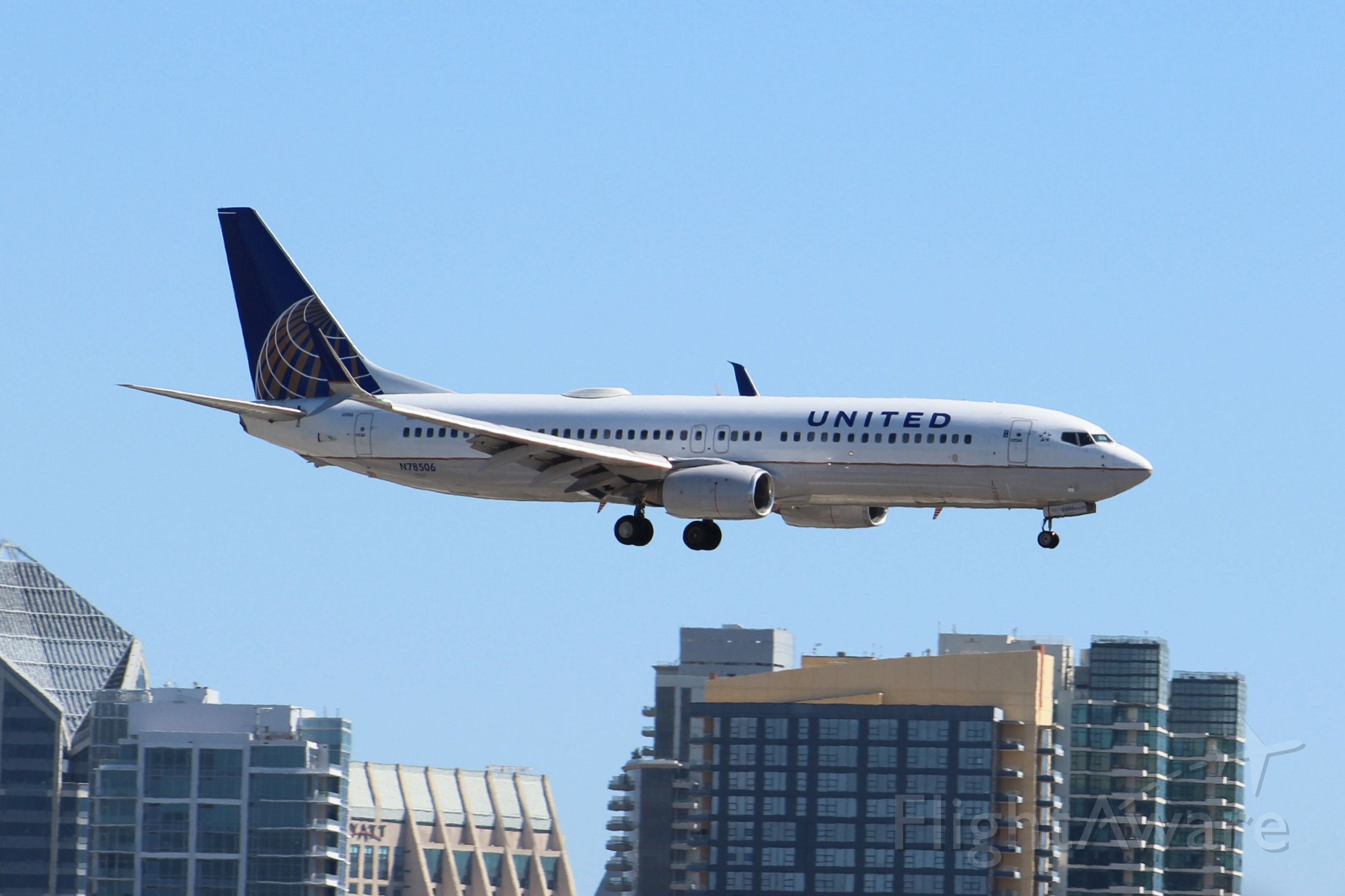 Boeing 737-800 (N78506) - Landing 27 with split scimitar wingtips. San Diego skyline visible in the background.