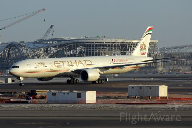BOEING 777-300 (A6-ETL) - Early morning arrival with the new terminal under construction in the background