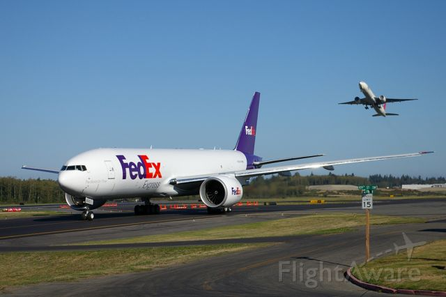 Boeing 777 (N850FD) - First FedEx 777 Freighter taxis for its delivery departure while a 777-300 departs on a test flight.