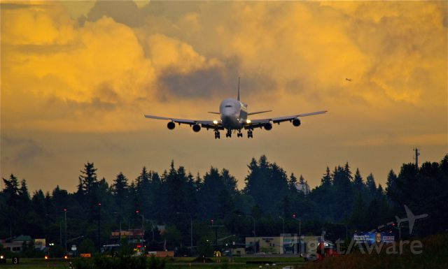 Boeing 747-400 (N747BC) - Dreamlifter N747BC on final to 34L at Paine Field about 8:30 last night. And you can just make out a heavy climbing out of SeaTac in the distance...