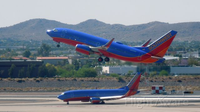 Boeing 737-700 (N242WN) - A Southwest 737 taking off over another company 737.