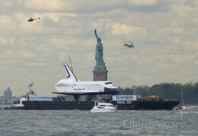 BOEING 737-300 (ELL101) - Space Shuttle Enterprise on the final leg of her journey to her new home at the Intrepid Air Sea and Space Museum in NYC, seen here on June 6, 2012 passing Lady Liberty as seen from Battery Park in lower Manhattan on the Hudson River, an Amazing site to witness.