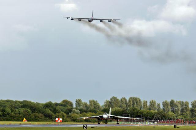 Boeing B-52 Stratofortress — - An RAF Vulcan on the runway at Fairford, UK, as a Buff flies overhead.