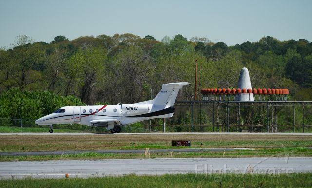 Embraer Phenom 300 (N68TJ) - Just landing at Dekalb Peachtree Airport.  Photographed from the observation stand.