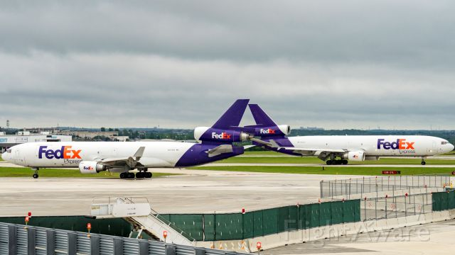 Boeing MD-11 (N573FE) - Tag team. Taxiing for departure while identical N595FE<br /> arrives 13R.