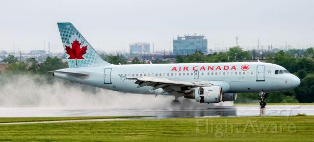 Airbus A319 (C-GITR) - Air Canada A319 C-GITR landing in rain thrust reverser deployed