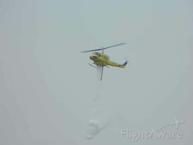 Beechcraft King Air 90 (N2777W) - UH-1H doing a water drop demo. 1/26/2012
