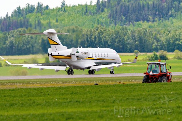 Canadair Challenger 350 (C-FMIX) - Taxing past a farm tractor after landing.