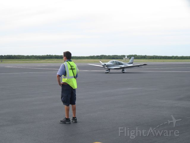 Piper Cherokee (N208GG) - AOPA Get Your Glass 2008 prized Archer II. Resting on the ramp of Marthas Vineyard Airport with MVY VOR in the background and a ramp attendant awaiting arrivals.