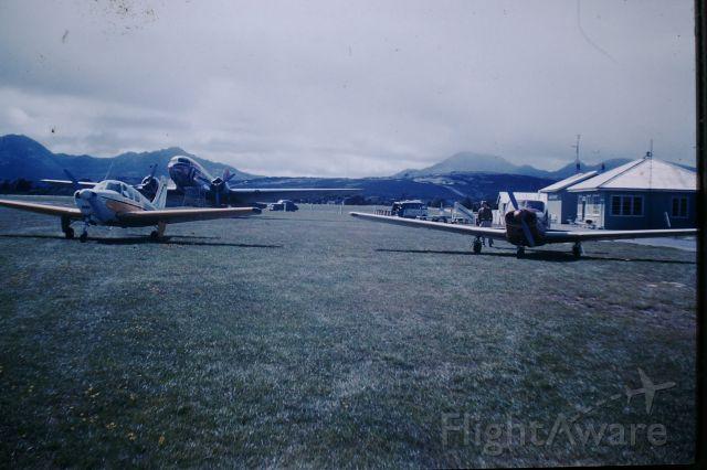 Beechcraft 35 Bonanza (VH-BIB) -  bonanza, unknown comanchie, and Ansett-ANA DC3 parked on grass ,circa 1960