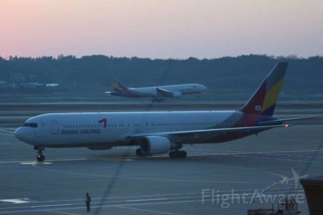 Airbus A330-300 — - An Asiana A330 touching down on Rnwy 34 at Incheon International Airport as another taxis to a gate.  Photographed just after sunset 01/16/2012.