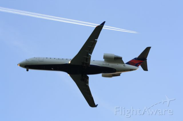 — — - Delta Regional jet on approach to rwy.13,as another jet passes above.