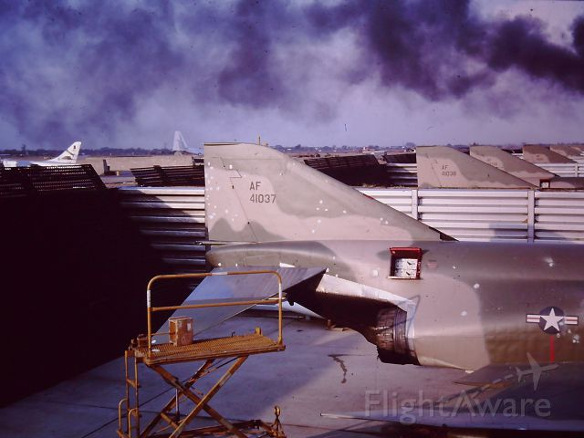 AFR41037 — - TAN SON NHUT AIR BASE, SAIGON, VIETNAM APRIL 1966 ATTACK ON THE base and the RF-4C SQUADRON.  ATTACK WAS AT NIGHT and this photo was late the next afternoon and there was something still burning (Not an RF4C).  Those doors open were the photo flash ejection system for night photography which ejected cartridges to light up the night.  The spots on 037 were shrapnel damage from mortars.