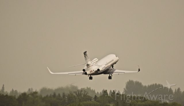 Dassault Falcon 900 (C-GJPG) - This Falcon gets airborne on a rainy, cloudy day on its way to Edmonton