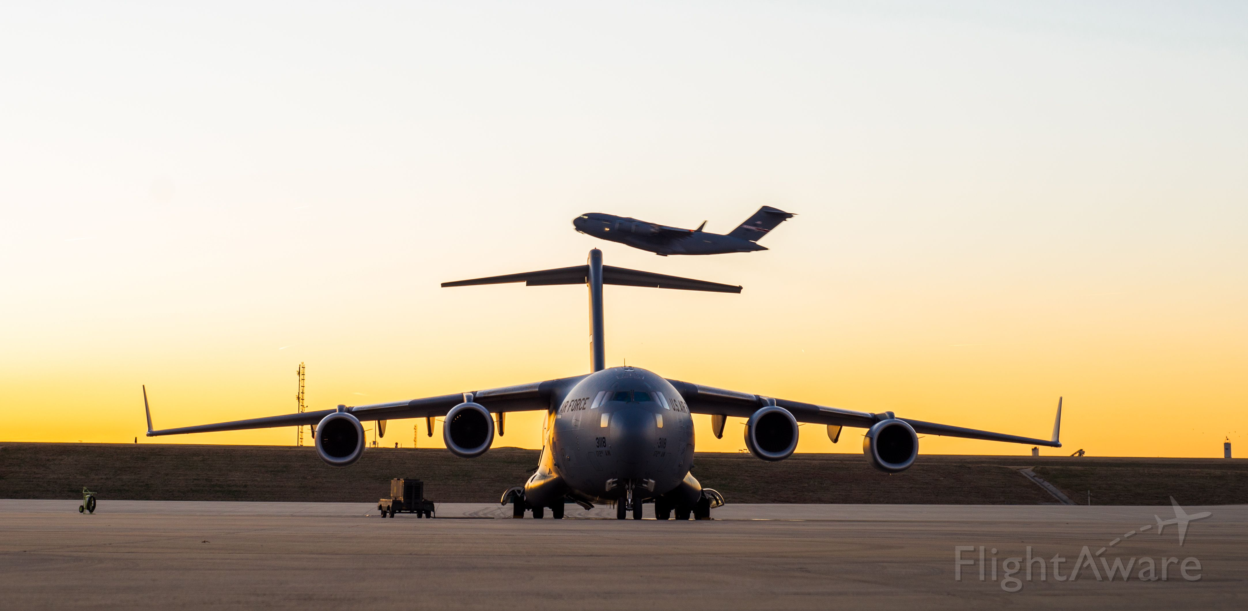 — — - A C-17 takes off while another rests on the ramp.