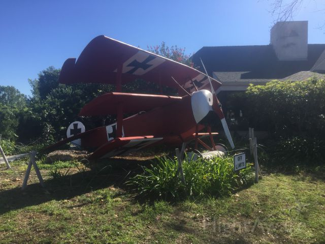 — — - A replica of the Red Barons Fokker triplane sits outside 94th Aero Squadron alongside Montgomery Field (MYF) in San Diego.