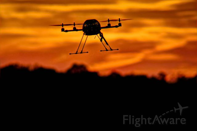 — — - A quadricopter drone hovers in the air as the sun sets.