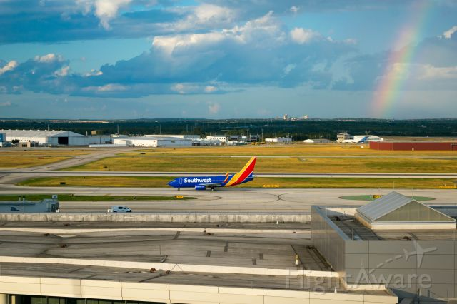 Boeing 737-700 (N7837A) - Southwest 737 taxiing to runway 12r with a rainbow in background