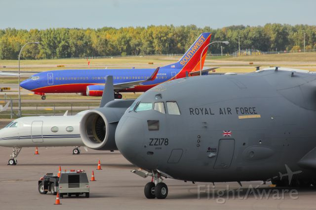 — — - A Southwest 737 passes behind a C17 from the RAF at the Minneapolis/St. Paul airport.