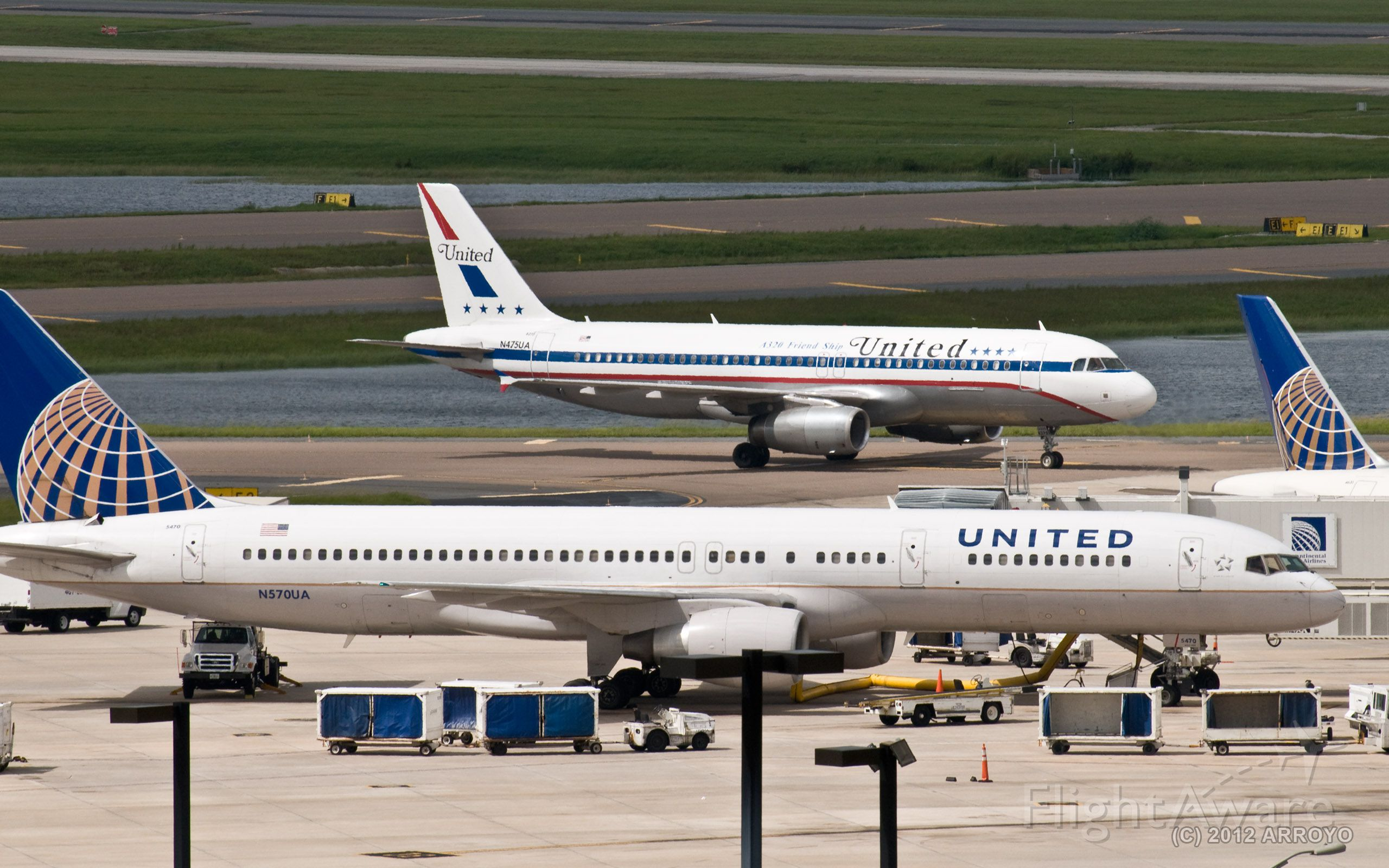 Boeing 757-200 (N570UA) - United Airlines Aribus A320 (Friendship One) special livery plane (N475UA) passes behind a Boeing 757-200 (N570UA) parked at gate 39 at Orlando International Airport (MCO).  United currently operates 10 gates in Terminal B Airside 3 at MCO.