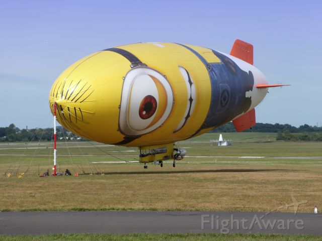 """— — - This Airship image is representing a character from the Animated Movie Series """"Despicable Me"""" and is called a """"Minion"""".  The image is certainly strange enough to confuse the cat at the right corner of the picture. This Airship is tethered here in the Summer of 2013."""