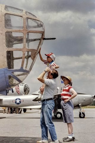 """Consolidated B-24 Liberator — - """"Touching the Past""""<br /><br />A young boy is held up by his father with his grandmother looking on, so he can touch the nose of a B-24.<br /><br />Digital image processed from a photo taken and scanned a long time ago"""