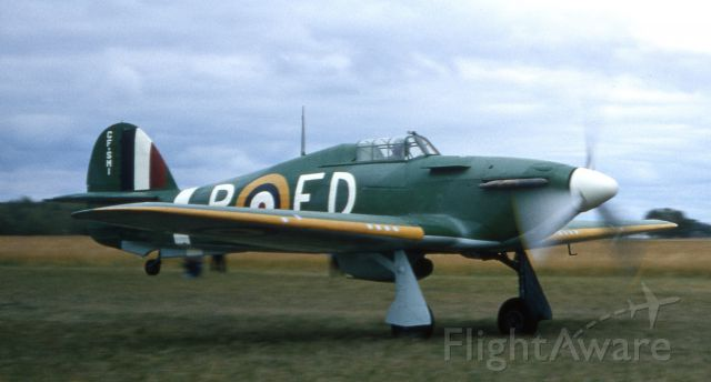 """— — - August 1965, Carman, Manitoba.  Bob Diemert rebuilt this WWII Hurricane at his grass strip near Carman, Manitoba.  This take-off photo was taken a few days after he """"accidentally"""" took off while doing high speed taxi tests..."""