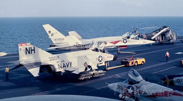 """15-3002 — - An F4B of VF-114 loaded with 12 high drag(Snake Eye) Mark 82 bombs and 4 AIM-7 Sparrow air to air missiles is spotted forward on USS Kitty Hawk for a strike package launch into Route Pack 6B from Yankee Station in the South China Sea Jan. 1967.  On 15 Apr 1968 F4B BuNo 153002 operating as Linfield 202 and F4B BuNo 153043 flying as Linfield 214 were lost in a mid-air collision over water while jinking in an attempt to break fire control radar lock on. The crews, LCDR John F. Farnsworth, LTJG Gerald K. Baer, pilots, and LTJG Joseph M. Sarnecky, LTJG Roy L. McCready, RIOs, ejected, and despite heavy 37-50-100mm fire from the beach, were rescued by helo and returned back aboard Kitty Hawk. Picture made from 06 level """"Vulture's Row""""."""