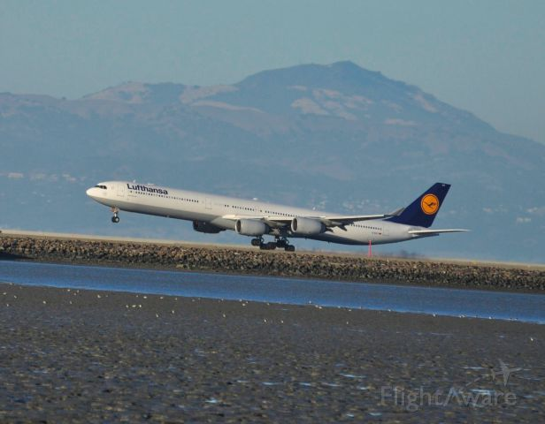 Airbus A340-600 (D-AIHT) - Lufthansa 458 just as the main gear wheels touchdown on runway 28 L